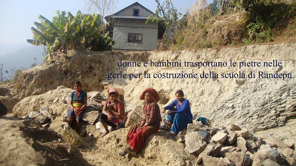 Donne-e-bambini-trasportano-le-pietre-nelle-gerle-per-costruire-la-scuola